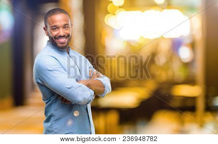 African american man with beard with crossed arms confident and happy with a big natural smile laughing at night
