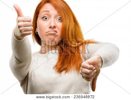 Beautiful young redhead woman confused with thumbs up and down, trying to take a decision expressing doubt and frustration isolated over white background