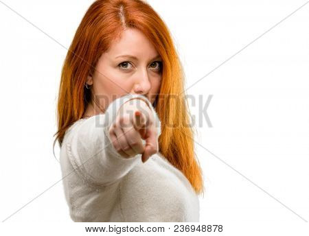 Beautiful young redhead woman pointing to the front with finger isolated over white background
