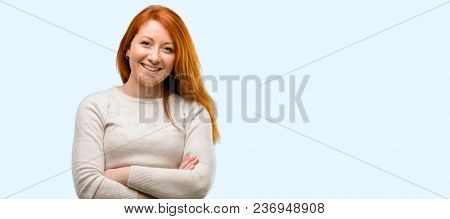 Beautiful young redhead woman with crossed arms confident and happy with a big natural smile laughing isolated over blue background