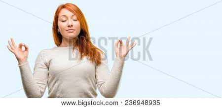 Beautiful young redhead woman doing ok sign gesture with both hands expressing meditation and relaxation isolated over blue background