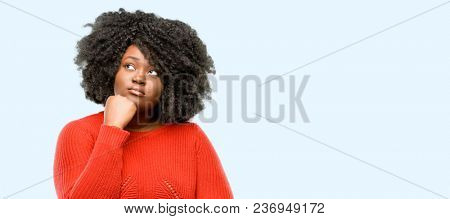 Beautiful african woman thinking and looking up expressing doubt and wonder, blue background