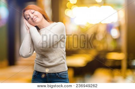 Beautiful young redhead woman tired and bored, tired because of a long day overworking at night