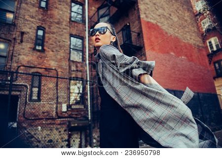 Fashionable Young Asian Girl Walking On City Street Wearing Stylish Outfit