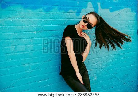 Beautiful Young Asian Girl With Long Hair Wearing And Black T-shirt Posing In Front Of Blue Wall