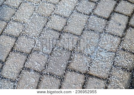 Melting Salt On The Sidewalk In Winter Season