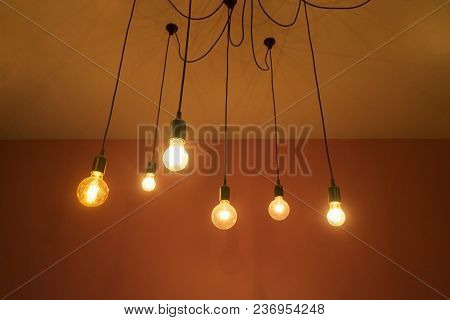 Light Bulb Hanging On Ceiling On Orange Background. Light Bulb Hanging With Black Electric Wire.