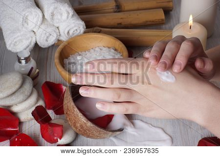 Female Hands Rubbing Lotion, Spilled Milk For Spa Procedures In The Background.