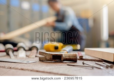 Equipment On Wooden Desk With Man Working In Workshop Background.