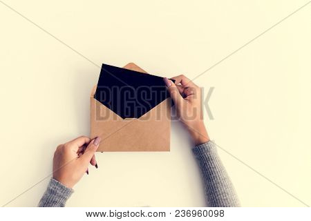 Woman hands holding envolope on white background