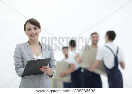 Woman manager holding clipboard on blurred background with mover