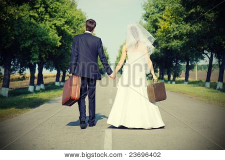 Couple Holding Suitcases On  Road