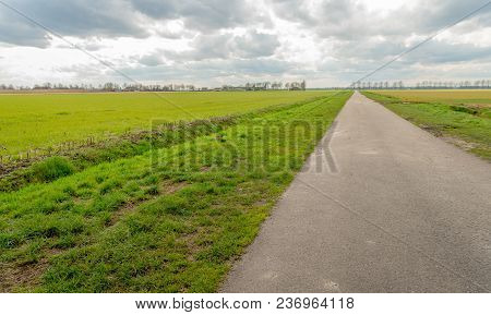 Seemingly Endless Country Road In An Agricultural Landscape With Fresh Green Grass Next To Ditches I