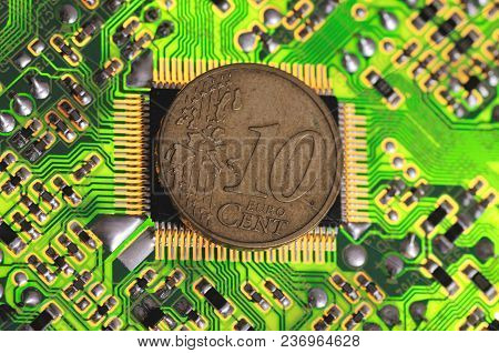 Euro 10 Cent Coin On Printed Circuit Board.