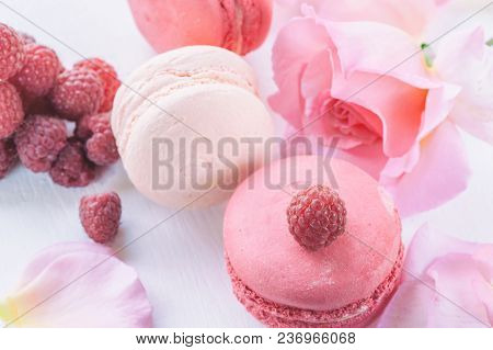 Macarons With Raspberries, Marshmallows On The Background Of Beautiful Flowers Roses. Dessert Close-