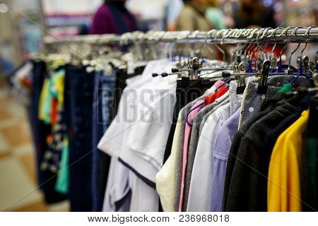 Children Clothes On Hangers In A Room. Wardrobe With Boy's Clothes On Hangers. Shopping And Consumer