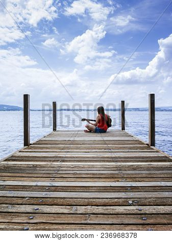 Photo Of A Young Woman Playing Her Acoustic Guitar On A Dock On A Lake.