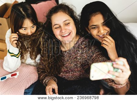Teenage girls using a smartphone to take a selfie in a bedroom hangout and friendship concept