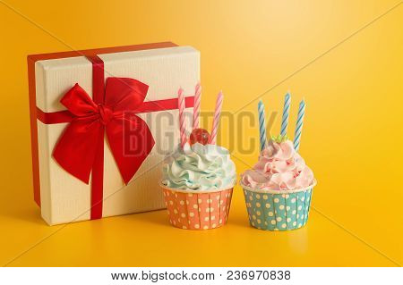 Tasty Birthday Cupcake And Gift Box On Yellow Color Background