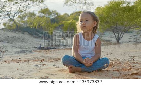Little Child Girl Sits At Desert And Pondering Somethink With Thousand-yard Stare. She Pours Sand Fr