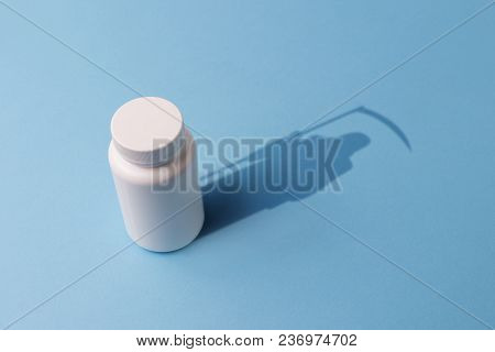 Plastic Bottle With Pills And A Shadow In The Shape Of Death With A Scythe. The Concept Of Death Fro