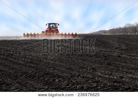 Modern Red Tractor In The Agricultural Field Mechanism. Tractor Plowing Land. Harvester Sowing Wheat