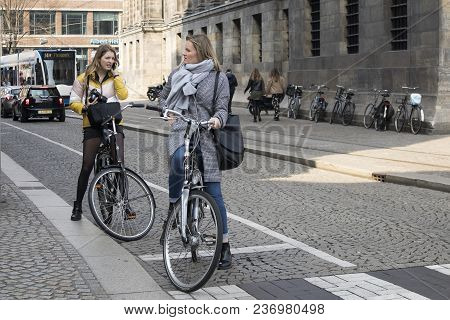 Amsterdam, Holland - 14 April 2018 View Of Bicyclist On Amsterdam Street, Netherland. Two Girls On T
