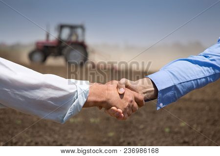 Two Businessmen Shaking Hands In Field With Tractor Working In Background. Agribusiness Concept