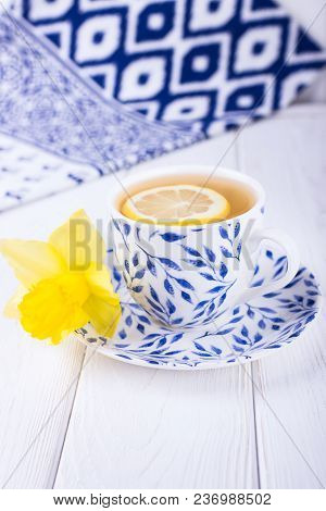 Lemon Tea And Yellow Daffodil On A White Wooden Background. Free Space