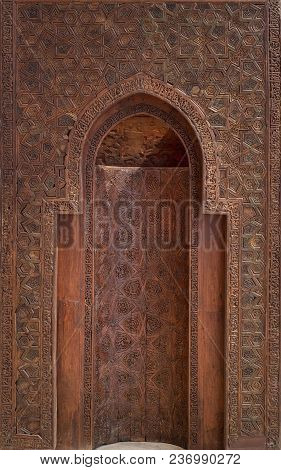 Fatimid era style wooden sculpted mihrab (niche) in wooden wall decorated with floral and geometric patterns, Cairo, Egypt poster