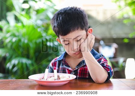 Asian Little Boy Boring Eating With Rice Food On The Wooden Table