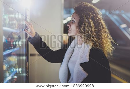 Attractive Woman On Transit Platform Using A Modern Beverage Vending Machine.her Hand Is Placed On T