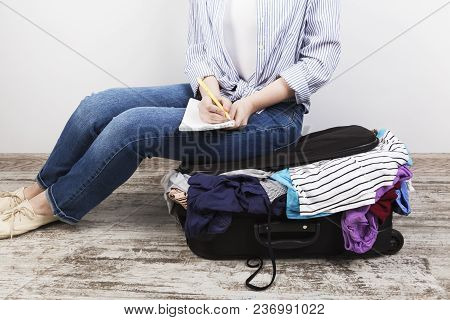 Young Girl Casually Packs A Black Suitcase