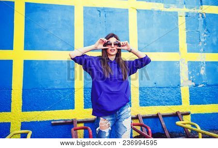 Amazing Charming Summer Young Woman With Long Hair In Jeans And Glasses Having Fun On Striped Yellow