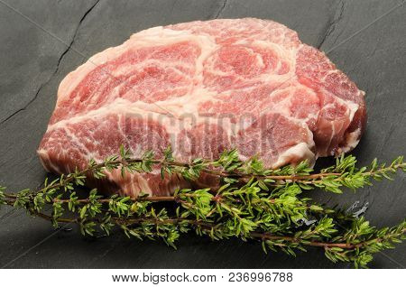 One Slice Raw Pork Neck With Thyme On Slate