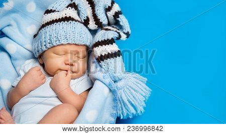 Newborn Baby Boy Sleep Over Blue Background, New Born Child Sleeping In Woolen Hat, Kid One Month Ol