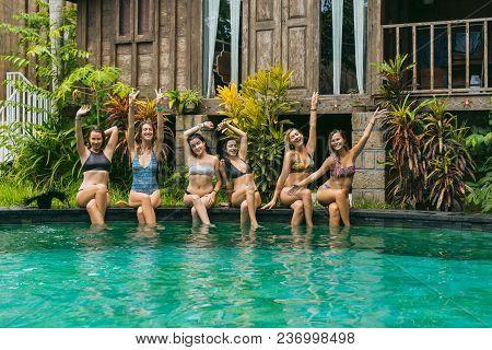 Happy Beautiful Girls In Swimwear Sitting At Swimming Pool And Smiling At Camera