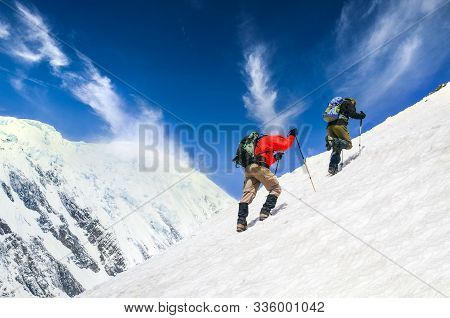 Two Mountain Trekkers On Steep Snowed Hill With Dramatic Sky Background