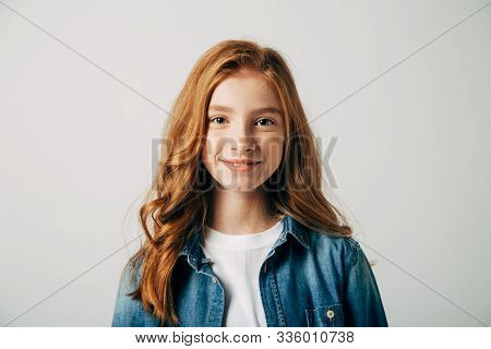 Red-haired Pretty Teenager Girl Smiling At The Camera. Blue-eyed Child With A Benevolent Emotion