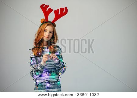 Beautiful Girl In A Garland Looks At The Camera. The Red-haired Teen Wrapped A Garland To Create A F