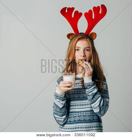 Red-haired Girl With Red Horns In A Sweater Is Very Fond Of Milk With Cookies A Night. She Did Not W