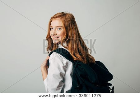 A Young Red-haired Girl Goes To School. Schoolgirl Looking Over Her Shoulder And Goes To Study Lesso