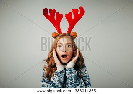 Girl With Deer Horns In A Sweater Smiles. She Is Shocked By The Gift For The New Year. Incredible Di