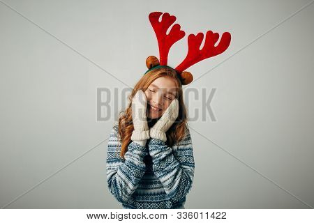 The Girl In A Sweater With Red Horns Smiles, Warming Her Face With Gloves On Her Hands. Warm Knitted