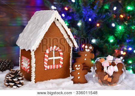 The Hand-made Eatable Gingerbread House, Little Men And Candy, New Year Tree With Garland In Backgro