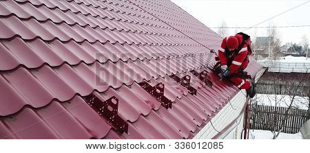 Moscow, Russia - February 15, 2019: Worker Does The Installation Of The Roof Of The House. Installat