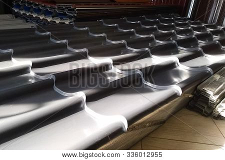 Sheets Of Metal In The Warehouse Of Roofing Building Materials. Modern Roof Made Of Metal. Corrugate