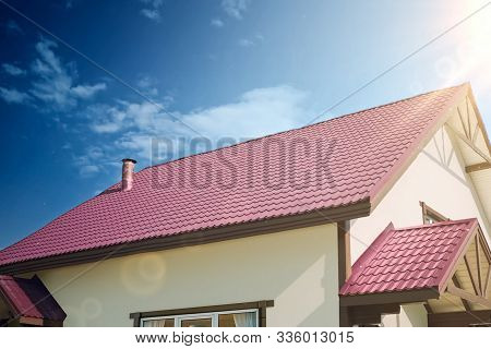 Sun Rays Over The Roof Of The House. Modern Roof Made Of Metal. Corrugated Metal Roof And Metal Roof