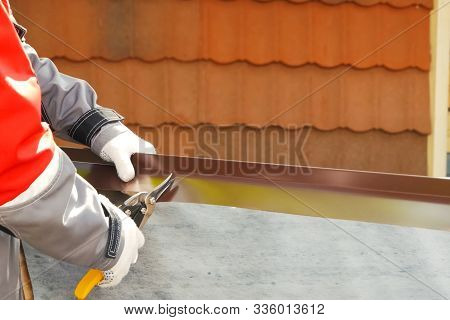 Worker Shears A Sheet Of Roofing Metal. Scissors For Metal.