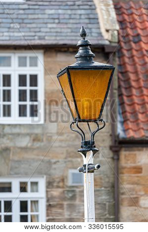A Weathered Old Traditional Street Lamp With Discoloured Glass
